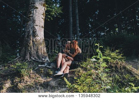 beautiful couple and a dog have a rest in the forest
