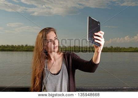 Beautiful young adult woman taking picture of herself, selfie shot with phablet leaning back metal fence in front of river. Instagram effect colorized shot.