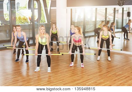 Group of young women in fitness class making exercises. Girls do squats with barbells. Healthy lifestyle in fitness club, training with weights.