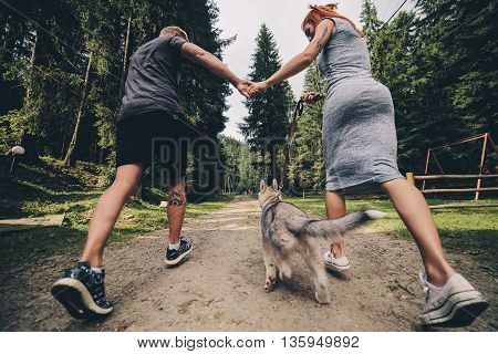 couple runs on road in the nature with dog to a house