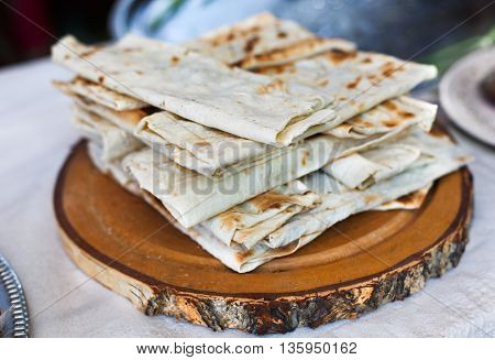 Stack of homemade whole wheat flour tortillas on a wood. Pitas for sale at picnic outdoors, closeup.