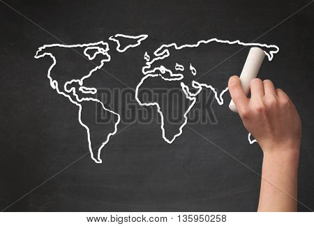 A teacher drawing the map of the world on a blackboard with a chalk