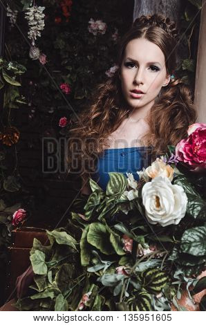 Spring fashion girl outdoors portrait in blooming dark garden. Beauty Romantic woman in flowers. Sensual Lady. Beautiful Woman Enjoying Nature. Romantic beauty in fantasy orchard.