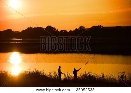 Silhouette of two fishermans fishing on the river at sunset