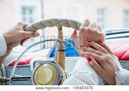 hands of man and woman on a car steering wheel