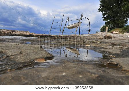 Fishing boat lifted on traditional crane seashore and reflection of the motive in a puddle of water