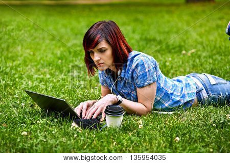 Beautiful young freelancer woman using laptop lying on the grass in the park.Happy smiling girl working online.Studying and learning using notebook computer.Freelance workbusiness people concept.