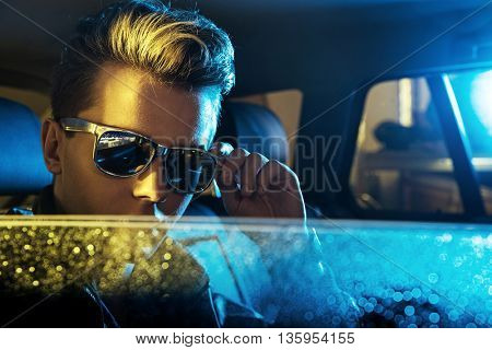 Handsome young man sitting in the car