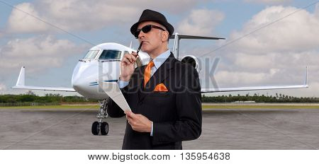 Business man next to a private jet thinking