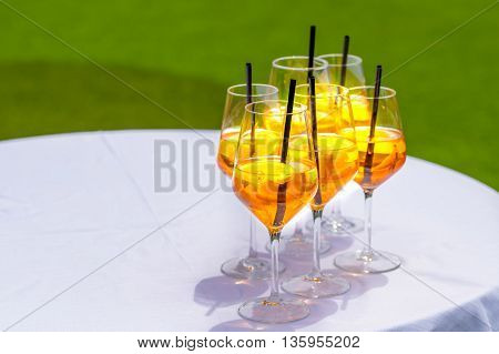 Popular Italian aperitif made with prosecco orange bitter and soda decorated with orange slices.Several glasses on white table with green background.