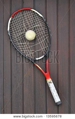 Broken Tennis Racket and old tennis ball on brown wooden floor