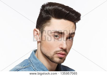 Closeup portrait of handsome man with bright black hair isolated on white background. Male showing modern hairstyle in studio.