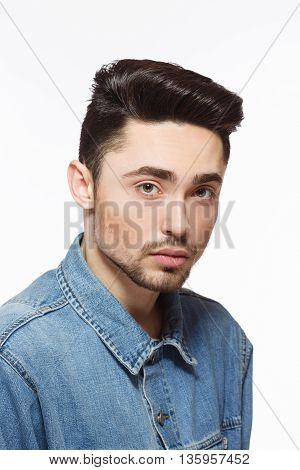 Portrait of model man demonstrating hisgorgeous black hair over white background. Male in jeans shirt with modern hairstyle in studio.