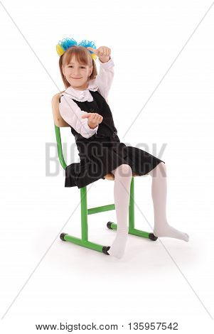 Schoolgirl sitting on the chair showing thumb isolated on white background
