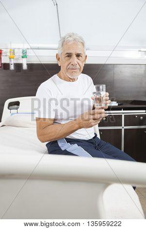 Senior Man Holding Water Glass In Rehab Center
