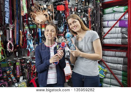 Mother And Daughter Holding Toys For Pet In Shop
