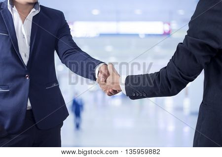 Two businessman shaking hands on blur of shop background