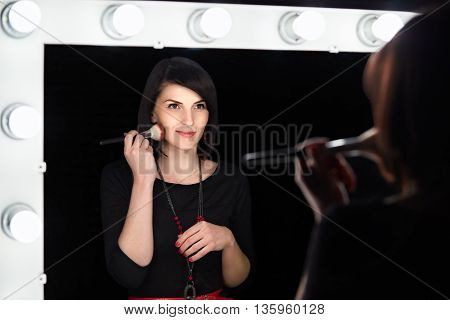 Fashion Model Applying Makeup In Dressing Room Mirror