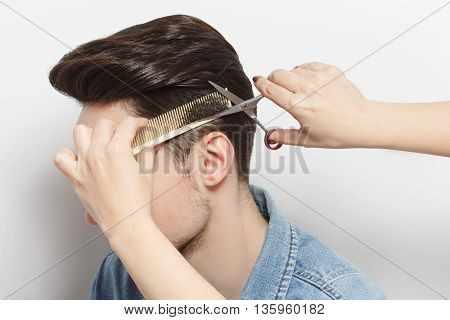 Portrait fo handsome man with black hair having haircut over white background. Hairdresser holding comb and scissors.