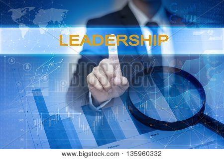 Businessman hand touching LEADERSHIP button on virtual screen