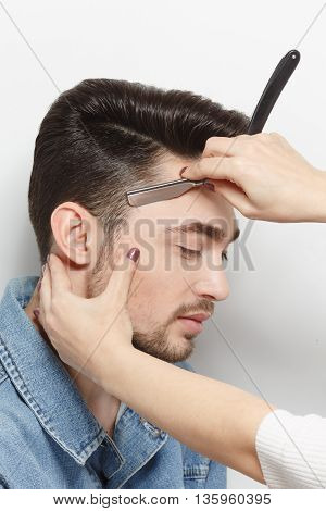 Modern hairdressing technologies. Studio shot. White background. Hairdresser cutting black hair of handsome man with blade.