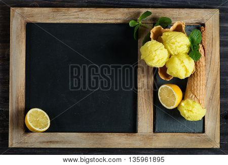 Lemon sorbet in a wafer basket and in a cone on a black chalkboard for menu with copy space for your text.
