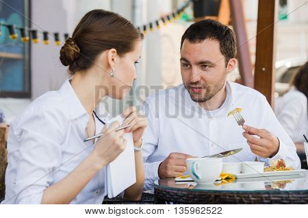 Successful manager sitting at business lunch with colleague and giving her instructions.