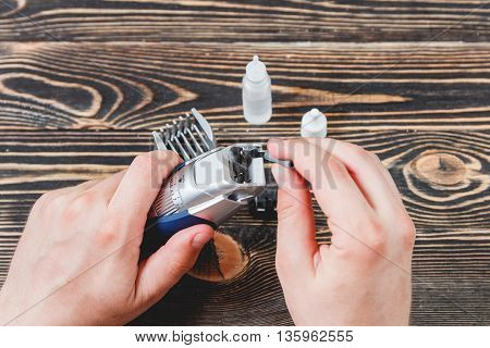 Cleaning Electric Razor, Hair Trimmer on a Wooden Table, Care Concept