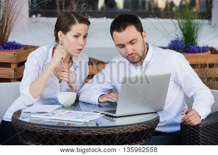 Businessman and bsuinesswoman working outdoor at street cafe.