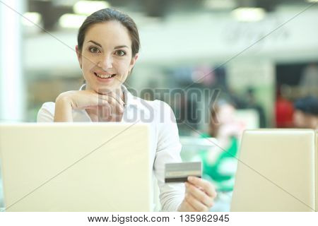 Smiling businesswoman doing online shopping through laptop and credit card in office
