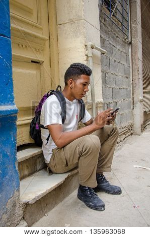 HAVANA - CUBA  JUNE 19, 2016: A young man checks his cell phone for messages while sitting on the stoop of his home, one of thousands of deteriorating and decaying buildings in La Habana Vieja.