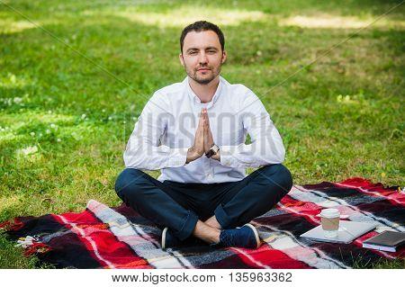 businessman outdoor do yoga exercise holding palms in namaste gesture.