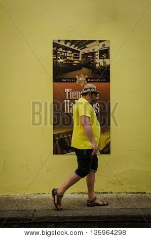 HAVANA - CUBA JUNE 19, 2016: A man walks by a building recently painted bright yellow with a poster selling cigars is posted on the wall.