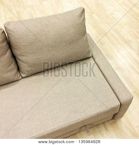 Elegant sofa-bed on wooden floor. Modern style furniture.
