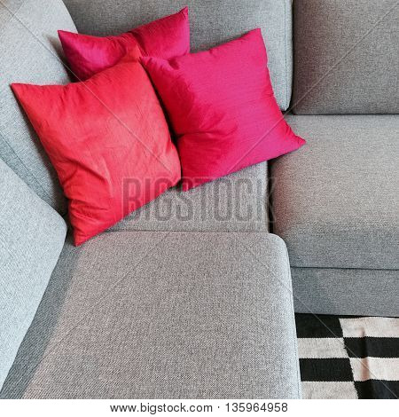 Comfortable gray corner sofa with silky red cushions.