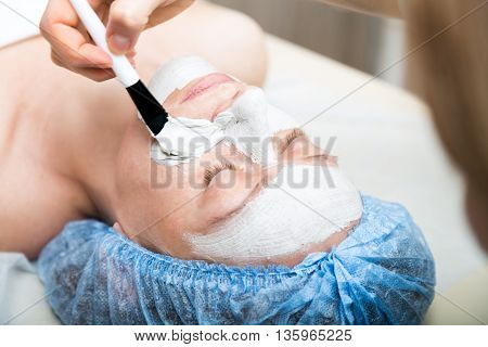 Young woman lying down in a spa salon and having a facial beauty treatment. The cosmetic procedures for the face. Beauty treatments in the spa salon. Facial Skin Care.