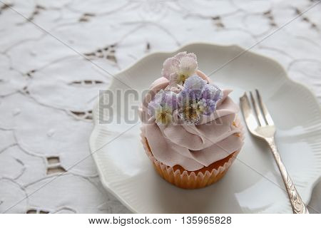 Purple Cupcakes With  Sugared Edible Flowers On Vintage Plate.