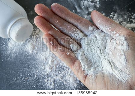 Talcum powder on hand on black background