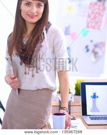 Young attractive fashion designer standing by desk in office, holding folders.