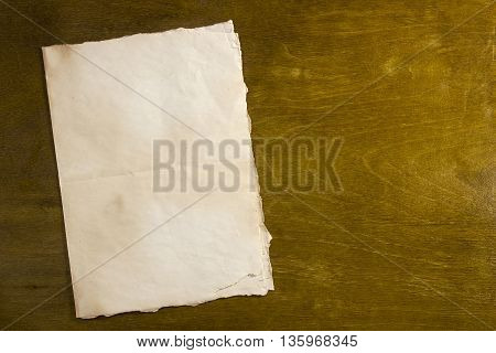 Dirty old sheet of paper on dark wooden background