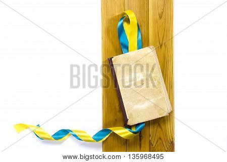 Yellow blue satin ribbons and a book on a wooden background