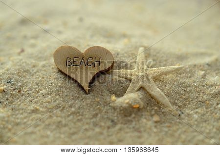 Depth of field beach text carved/engraved in heart shape piece of wood on sand beach with starfish