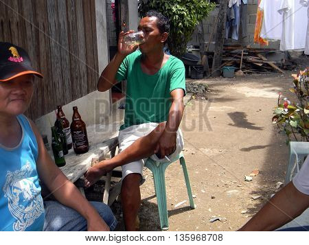 CEBU CITY, CEBU / PHILIPPINES - JULY 29, 2011: A man drinks a glass of San Miguel Beer outside of a home in Cebu City.