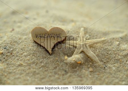 Depth of field valentine text carved/engraved in heart shape piece of wood on sand beach with starfish