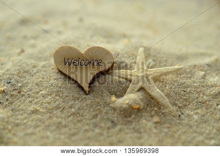 Depth of field welcome text carved/engraved in heart shape piece of wood on sand beach with starfish