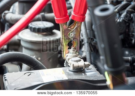 red clamp on car battery. for charging battery car with electricity. selective focus at between red clamp and battery pole