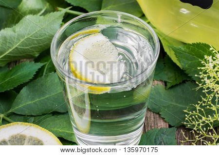 Glass of water with Elderflower Syrup and Lemon on Old Wooden Table