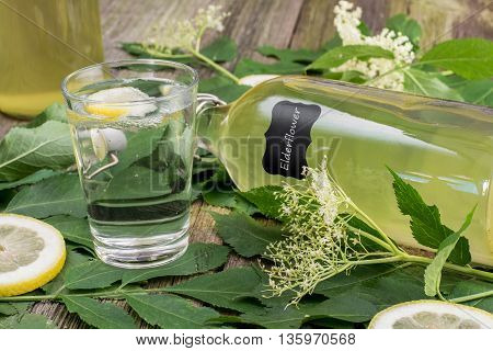Glass of water with Elderflower Syrup and Lemon with lying Bottle of Elderflower Syrup on Old Wooden Table