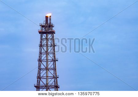 Tower Chimney Of Oil Refinery With Fire On Top On Blue Cloud Sky Background, Business Industry Facto
