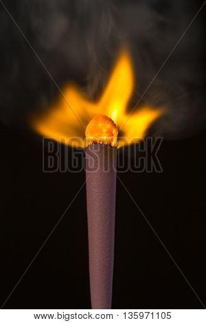 big burning match closeup on a black background